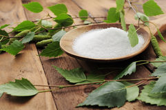 Xylit (birch sugar) on a wooden spoon. With birch branches around on a wooden table Royalty Free Stock Image