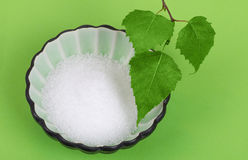 Xylitol birch sugar in bowl with birch leaves over green Royalty Free Stock Photography
