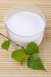 Xylitol birch sugar in glass bowl with birch leaves on bamboo mat. Xylitol birch sugar in a glass bowl with birch leaves on a bamboo mat. White granulated sugar stock image
