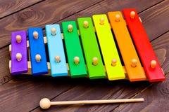 Xylophon auf altem braunem Holztisch Kind-` s Xylophon, gemalt in den Farben des Regenbogens lizenzfreie stockfotos