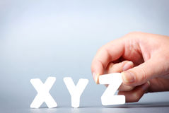 Xyz. A picture of female hand putting letters xyz in a row Stock Photo