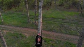 Yéndose volando el tiro aéreo de la muchacha deportiva activa del pelirrojo ponga en el árbol de pino en bosque conífero almacen de metraje de vídeo