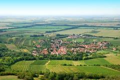 Żyźni zieleni winnicy i mała wioska w lecie Obrazy Stock