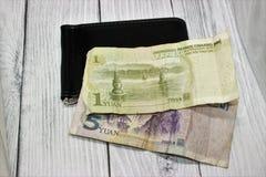 1 y 5 billetes de banco chinos de Yuan en un monedero negro en un fondo gris imágenes de archivo libres de regalías