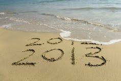 2012 y 2013 escritos en arena Fotos de archivo libres de regalías