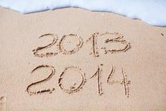 2012 y 2013 escritos en arena en la playa Imágenes de archivo libres de regalías