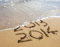 2013 y 2014 escritos en la arena Fotografía de archivo