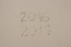2016 y 2017 escritos en la arena en la playa Foto de archivo libre de regalías