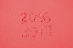 2016 y 2017 escritos en la arena en la playa en colores rojos Imagen de archivo