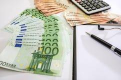 100 y 50 euros, calculadora, pluma en un fondo blanco foto de archivo