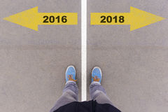 2016 y 2018 flechas del texto en la tierra, los pies y los zapatos del asfalto en f Imagen de archivo