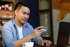 y x22; Haciendo la transferencia bancaria en línea, el hombre sostiene una tarjeta de crédito mientras que es ent imagen de archivo libre de regalías
