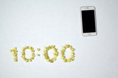 10:00 y teléfono del tiempo Fotos de archivo libres de regalías