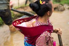 Y Ty, Vietnam - Maj 12, 2017: Etnisk minoritet fostrar med hennes lilla barn på det tillbaka arbetet på terrasserat fält Arkivbilder