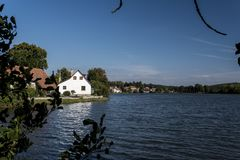 Y una casa blanca en un pequeño pueblo en los bancos de la charca Imagen de archivo libre de regalías