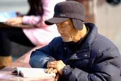 Ya'an China-An old man is looking at a book under the sun. At the Gallery bridge bridgehead,an old man in the sun to concentrate on looking at the book.Yaan Stock Photography