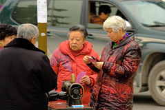Yaan China-Four old men playing poker cards on the street Stock Image