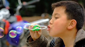 Yaan China-A little boy is blowing soap bubbles. At Peach Hill in Yaan,a little boy is blowing soap bubbles.Yaan China-Danchayuan photo stock images