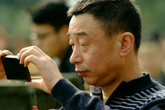 Yaan China-A man is to concentrate on using a mobile phone to Photograph. At Jinfeng temple,a man is to concentrate on using a mobile phone to Photograph.Ya'an Royalty Free Stock Photo