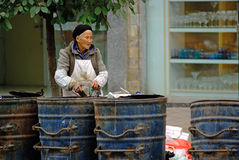 Yaan China-An old women picking up trash Stock Photos