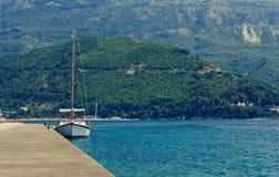 Yacht в причаливать с горами на предпосылке стоковая фотография