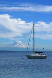 Yacht. A small yacht under the sunny blue sky with a mountain on the background Royalty Free Stock Image