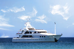 Yacht. A view of a luxurious white yacht anchored close to the coast under a beautiful blue cloudy day
