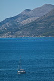 Yacht in the Adriatic sea, mountains, Croatia. Yacht sails over the Adriatic sea in front of the mountains, Croatia Royalty Free Stock Photo