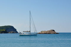 A yacht in the Adriatic sea and the rocky island. 2014 Royalty Free Stock Image