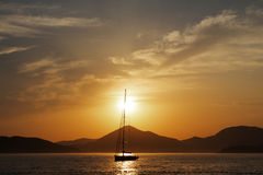 Yacht in the Adriatic sea at sunset. Beautiful gold sunset with a sailboat royalty free stock photo