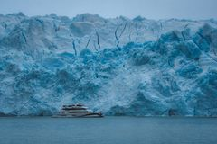Yacht against blue ice of glacier royalty free stock photography