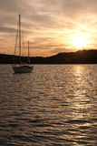 Yacht on anchor in the bay. With romantic sunset in background Stock Photography