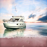 Yacht anchored on the beach with couples foot prints Stock Photo