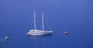 Yacht anchored to shore in Greece, Santorini Island. Blue water stock photography