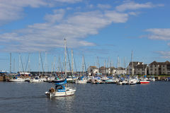 Yacht arriving in Tayport harbour, Fife, Scotland. A single yacht arriving under it's own power heads to join other yachts moored in Tayport harbour, Tayport stock photo