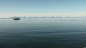 Yacht on background of icebergs, snow and ice in the Arctic Ocean. Iceland- 8 September 2016: Yacht on background of icebergs, snow and ice in the Arctic Ocean stock video