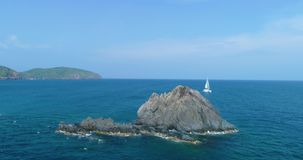 Yacht bianco, catamarano, navigante nel mare, vicino all'alta scogliera ed all'isola stock footage