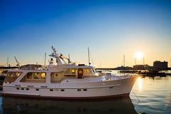 Yacht bianco in porto commerciale in mare al tramonto Fotografia Stock