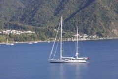 Yacht blanc ancré dans le compartiment bleu Image stock