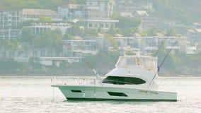 Yacht blanc de moteur ancré en mer propre calme avec les bâtiments modernes sur le fond Photo stock