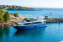 Yacht bleu naviguant lentement dans la baie photos stock