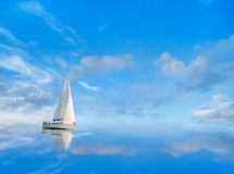 Yacht on blue sky. Reflected in calm water Stock Photos