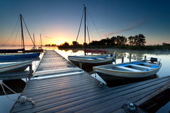 Yacht and boat by harbor at sunrise Stock Image