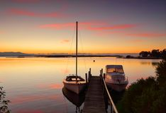 Yacht and boat moored to jetty at sunrise. A yacht and a boat are moored to a timber jetty at Mallacoota on sunrise Royalty Free Stock Photos