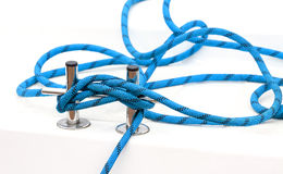 Yacht bollard with blue tangled rope on a deck. Stock Images