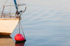 Yacht Bow Buoy. Yacht bow section anchored moored buoy on glassy sea ocean water stock photography