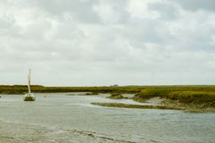 Yacht background. Lonely yacht at Brancaster Staithe harbour with Brancaster golf clubhouse in the distance Stock Images