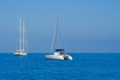 Yacht and catamaran on blue sea Royalty Free Stock Photos