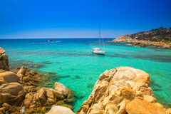 Yacht on Chia beach with red stones and azure clear water. Royalty Free Stock Photography