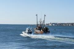 Yacht Chill-N passing fishing vessel Hustler. New Bedford, Massachusetts, USA - March 31, 2018: Yacht Chill-N passing fishing vessel Hustler as they head for Royalty Free Stock Photo
